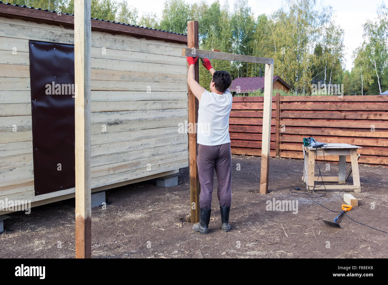 man measuring a wooden post on the level - Stock Image