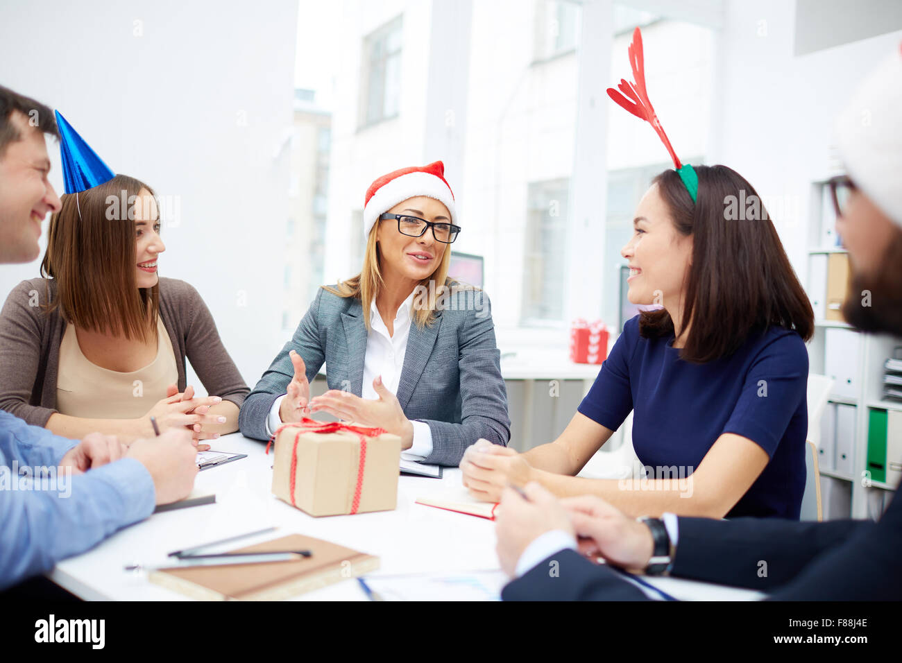 Young managers listening to their colleague at meeting in office on Christmas eve - Stock Image