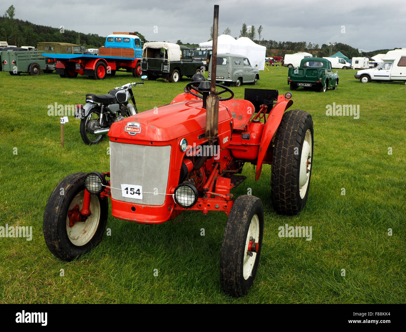 classic bright red vintage tractor resplendent in show field at agricultural show - Stock Image
