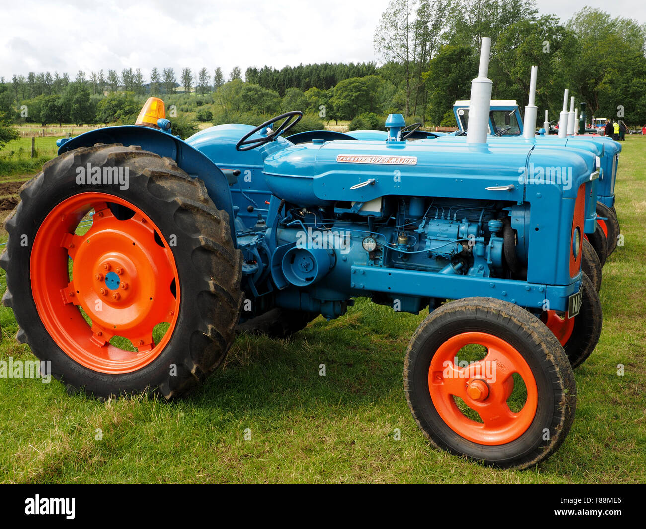 row of gleaming blue tractors with bright orange wheels in sunshine