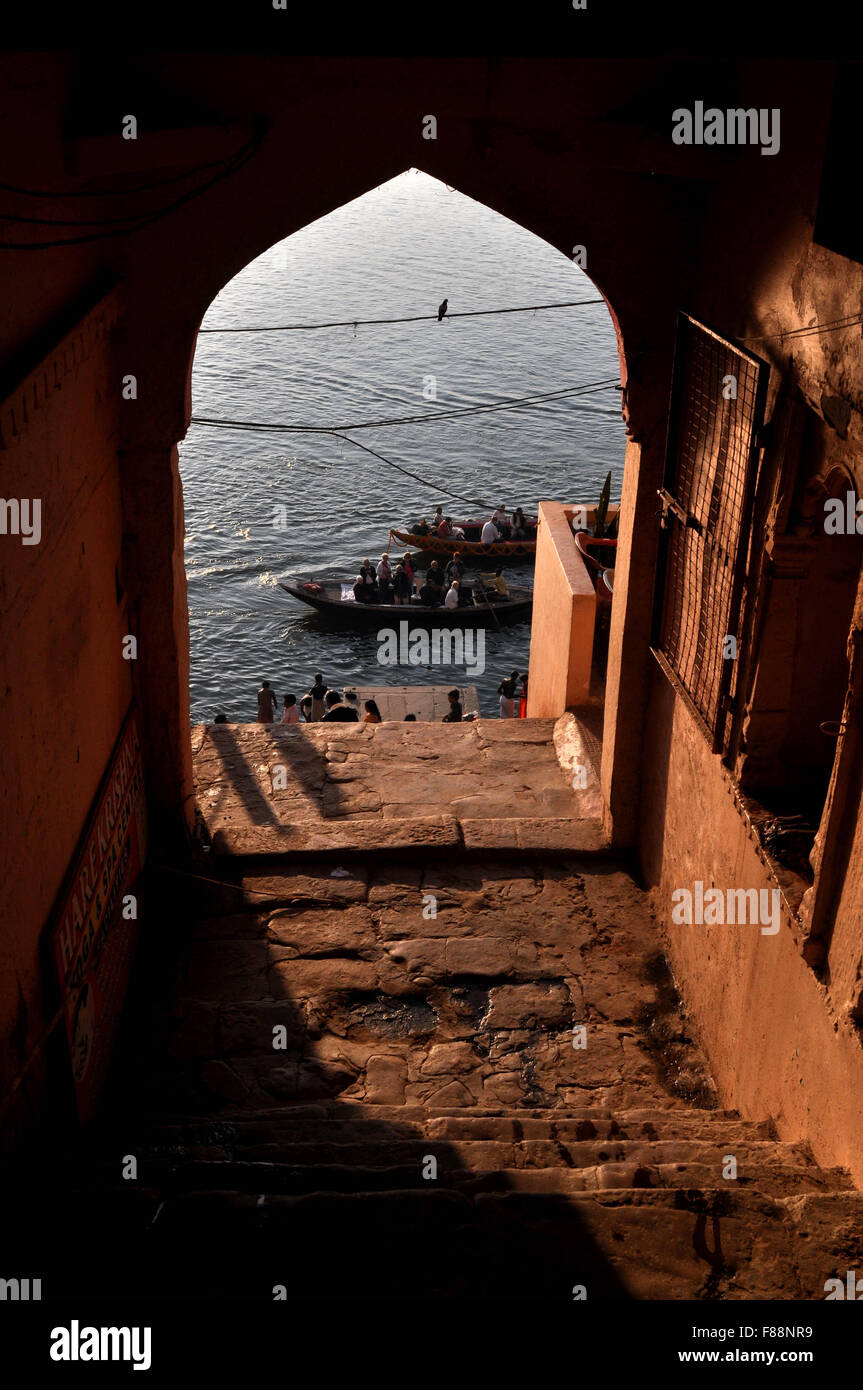 View from an old building gate some pilgrims using boats to cross Holy River ganges to reach their destination in Stock Photo