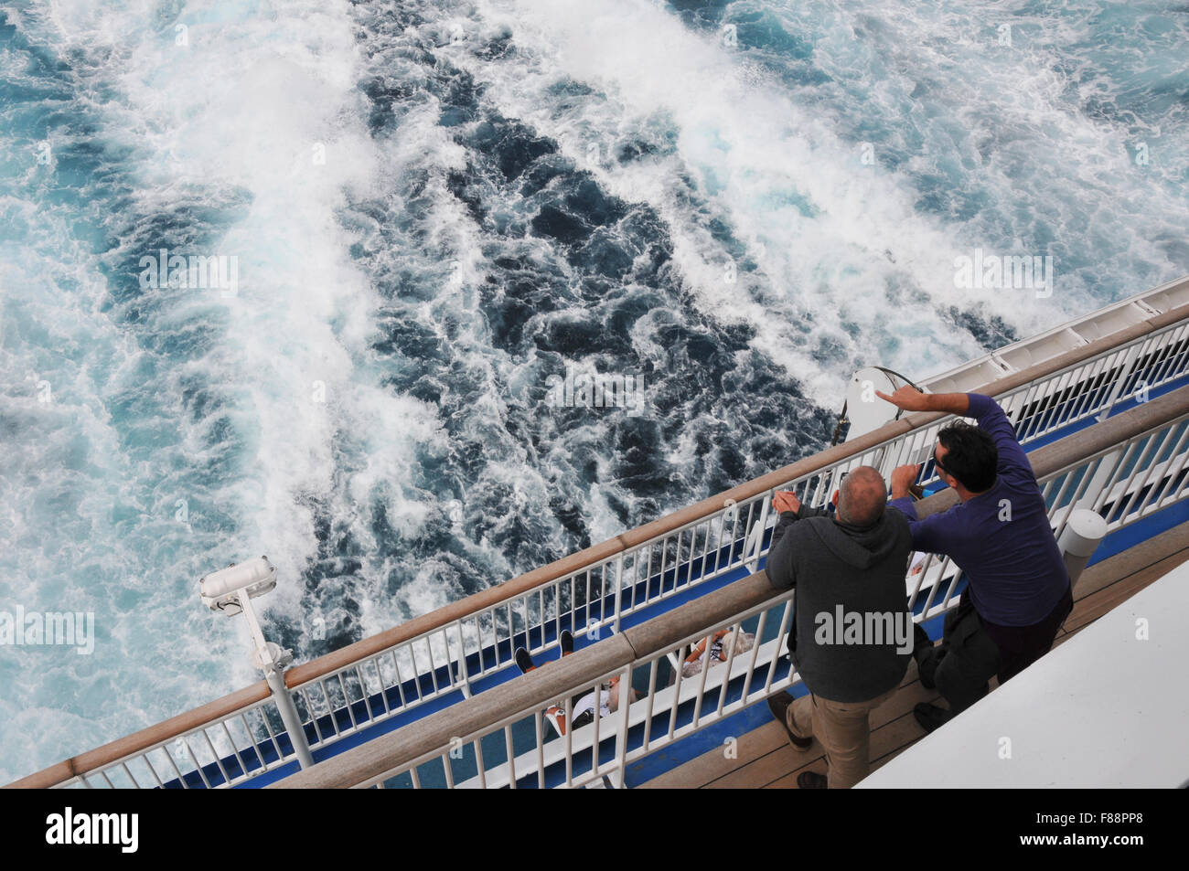 two men lean over rails and look out from ferry deck - Stock Image