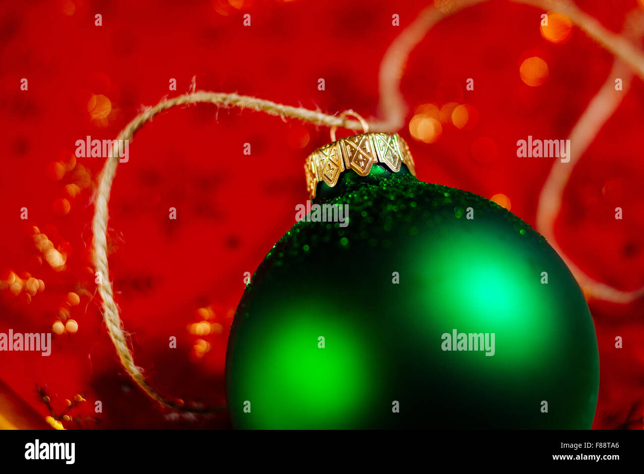 new year green ball on red holiday background close up - Stock Image