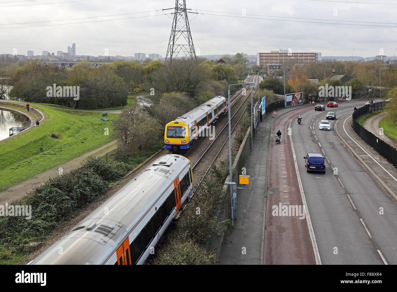 View of London Overground railway line in North London showing two trains and the adjacent road with bus lane and - Stock Image