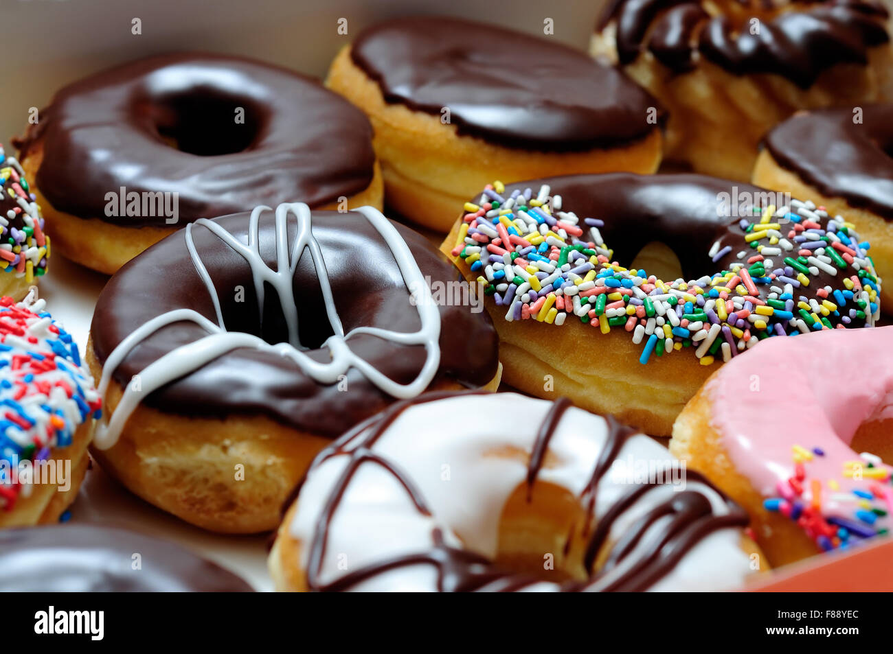 Picture of assorted donuts in a box with chocolate frosted, pink glazed and sprinkles donuts. - Stock Image