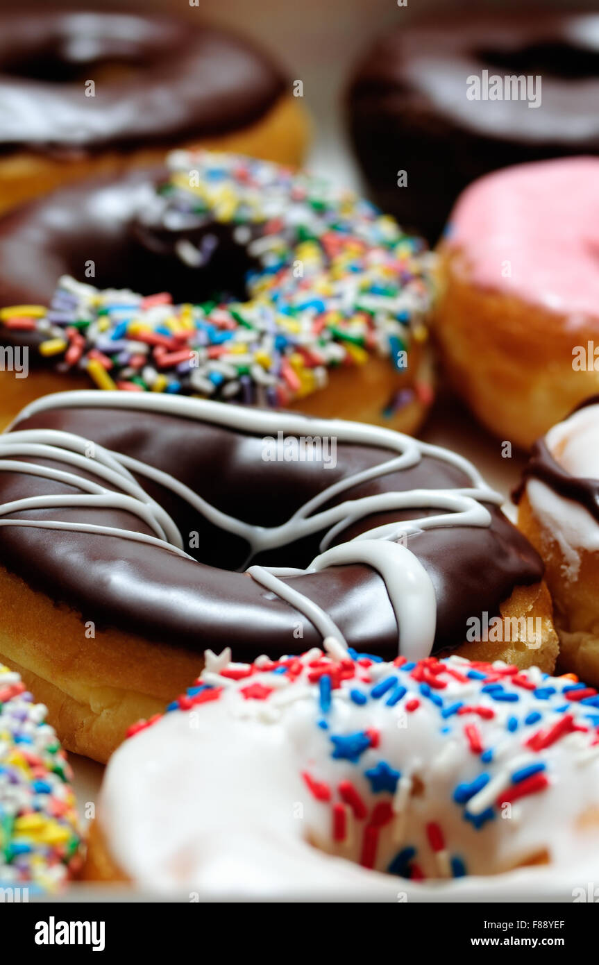 Assorted doughnuts with chocolate frosted, pink glazed and sprinkles donuts. - Stock Image
