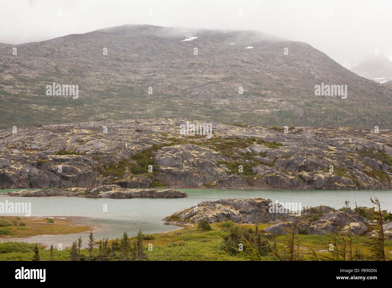 rugged yukon landscape with misty mountains - Stock Image