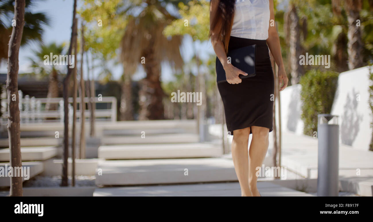 Elegant young woman walking through a park - Stock Image