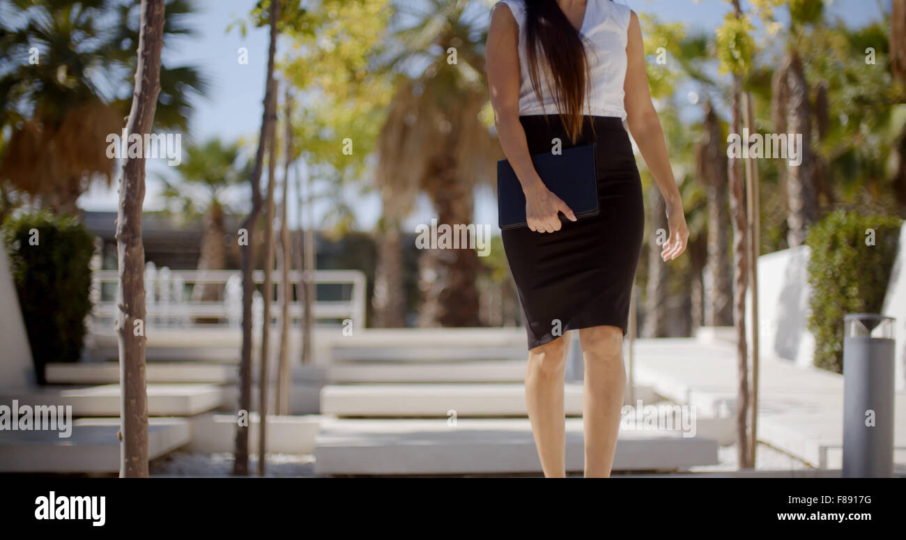 Young businesswoman walking through a park - Stock Image