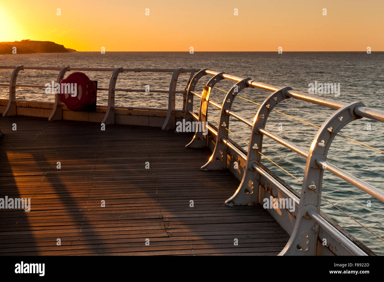 Sunset over Cromer cliffs from the pier - Stock Image