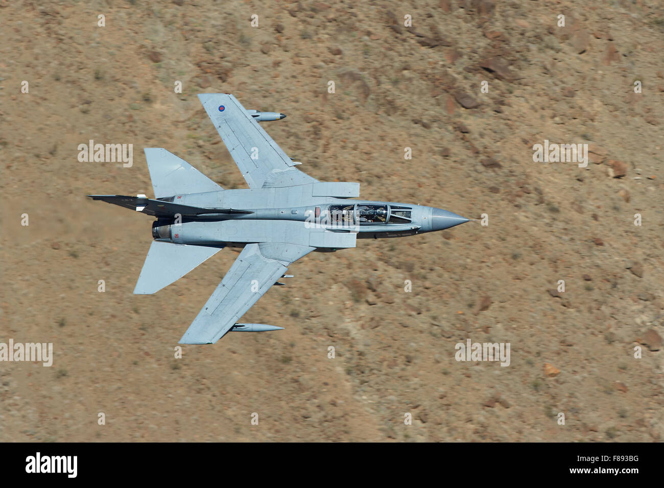 Royal Air Force Tornado GR4 Jet Fighter Flying At Very Low Level Through A Desert Valley. Stock Photo