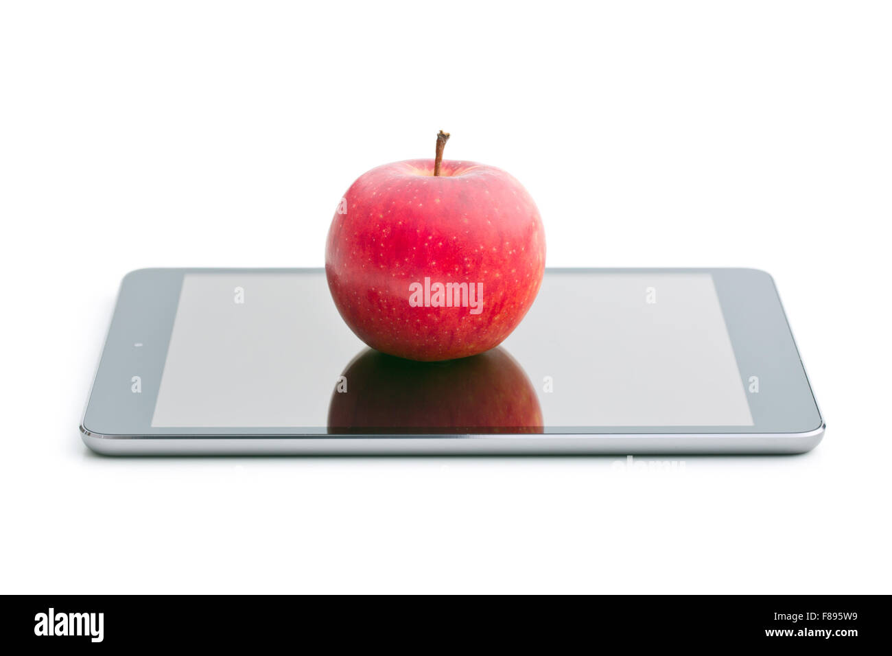 red apple and computer tablet on white background - Stock Image