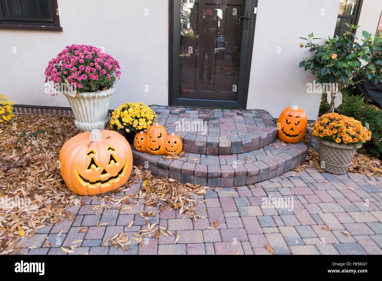 Halloween jack-o'-lanterns adoring the steps and sidewalk designed with randomly placed bricks.  St Paul Minnesota - Stock Image