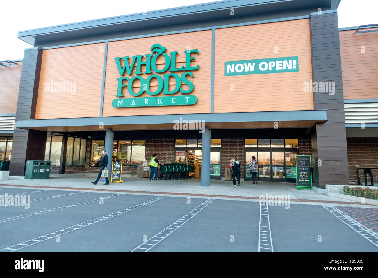 Customers entering Whole Foods Market and chatting with cart boy. Willowbrook Illinois IL USA - Stock Image