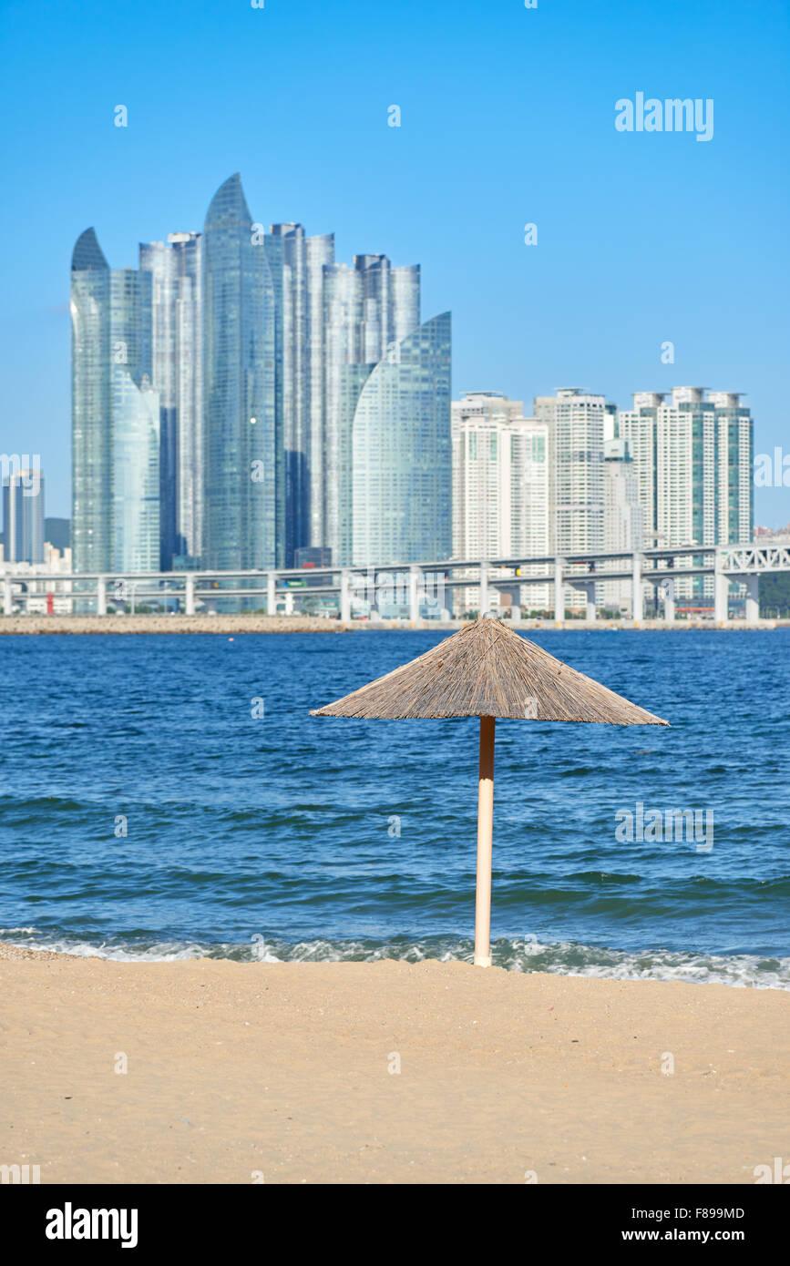 straw umbrella at Gwangalli beach with modern buildings in Marine city. Gwangan beach is located west of Haeundae - Stock Image