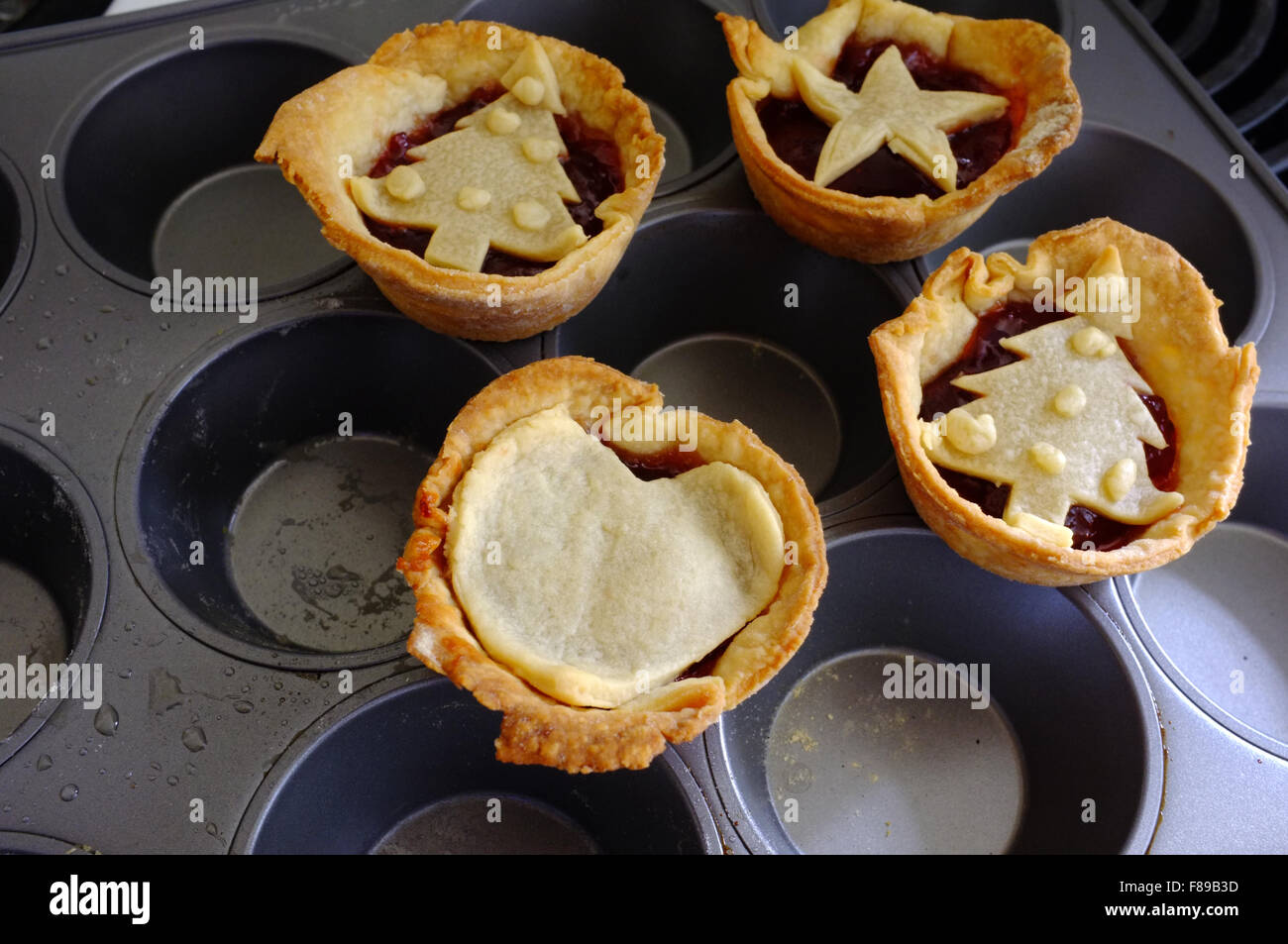 Homemade jam tarts sitting on a baking tray. - Stock Image