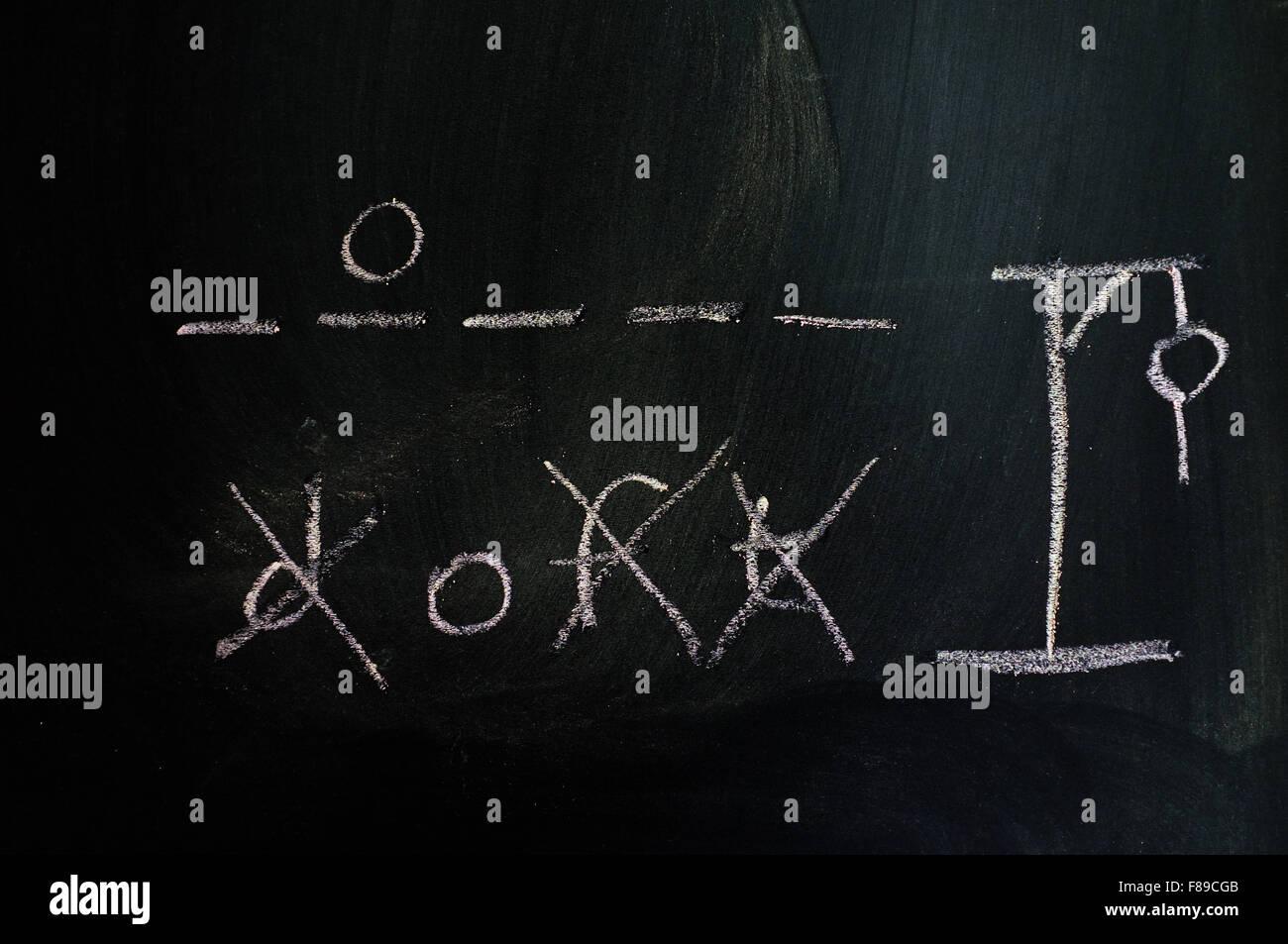 A game of hangman drawn on a blackboard in chalk. - Stock Image