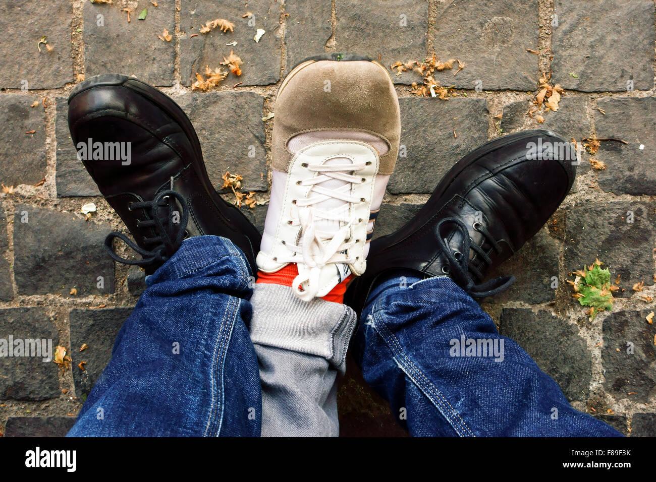 Overhead view of three legs, three feet, three shoes - Stock Image