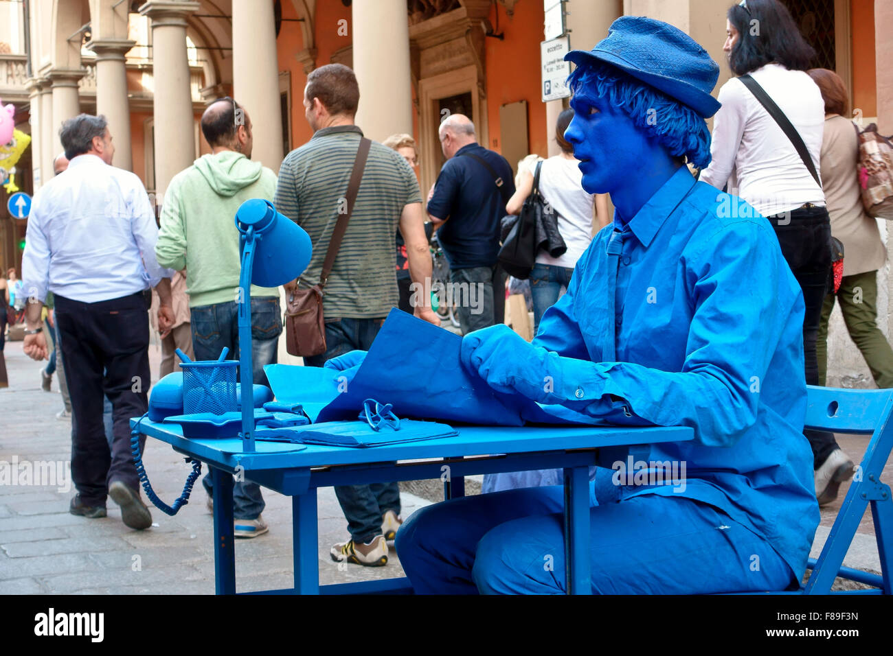 Blue painted man street performer, human statue, sitting still at a desk, on a busy street. Office in the street. - Stock Image