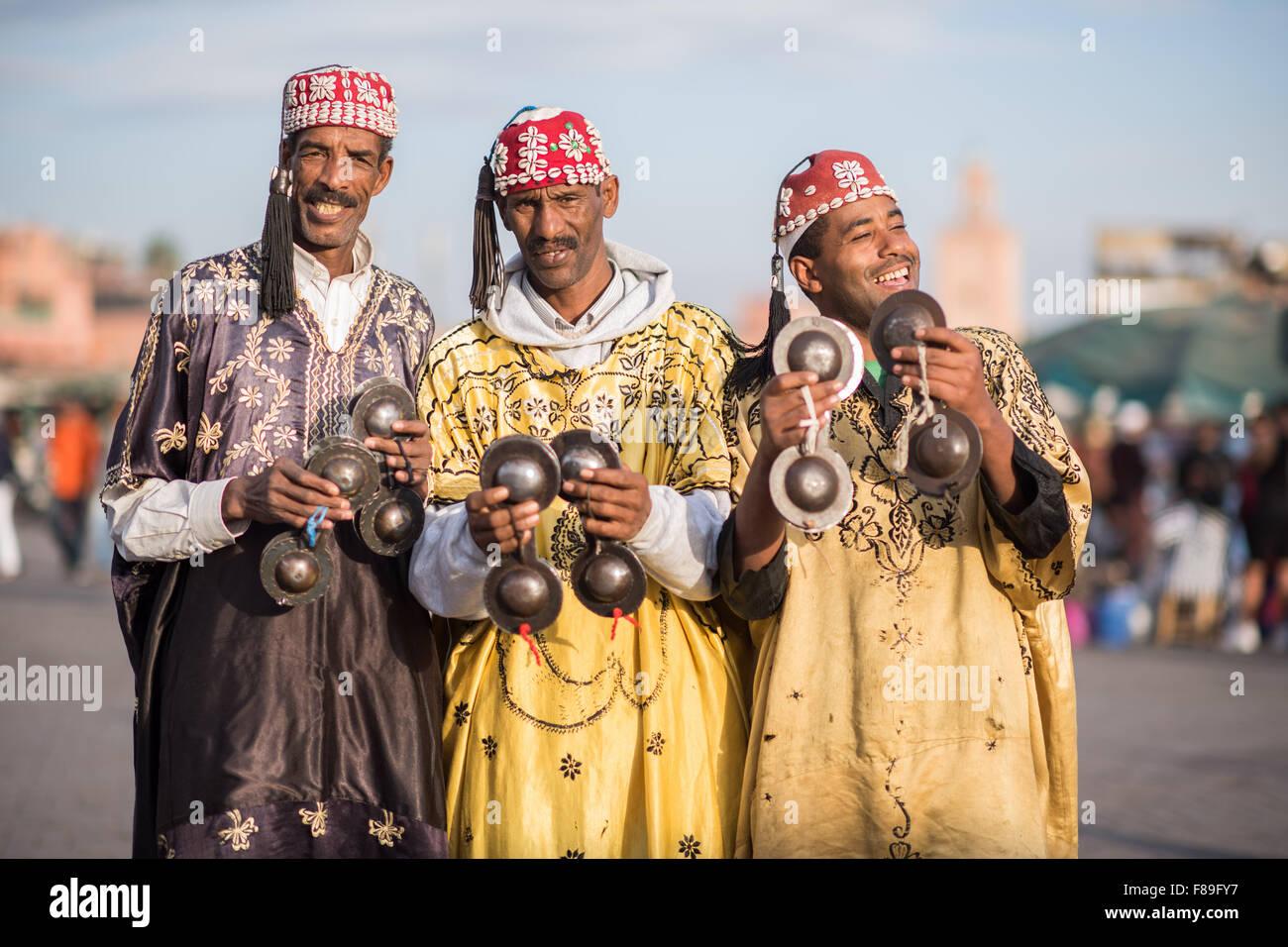 Three Gnawa musicians in traditional dress performing at Jemaa el-Fnaa in Marrakesh Stock Photo