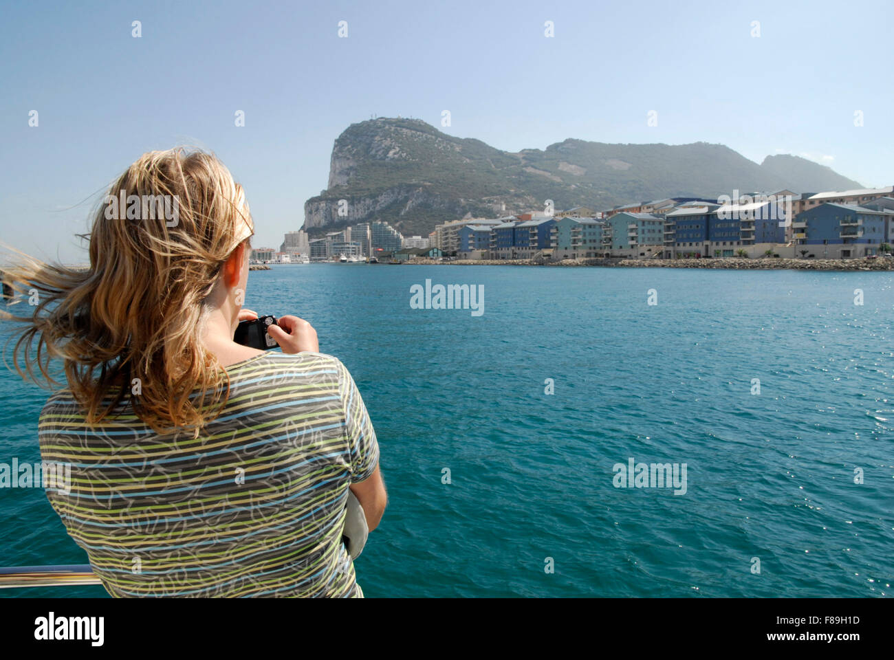 Gibraltar from the sea with the Rock in the background and new development in the middle ground. Tourist in foreground. Stock Photo
