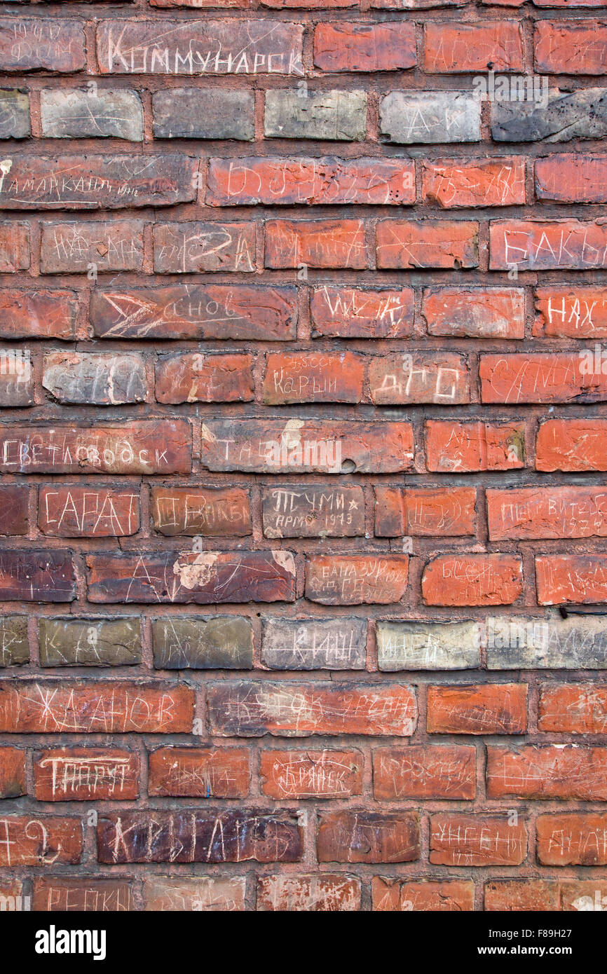A red brickwall covered with writings - Stock Image