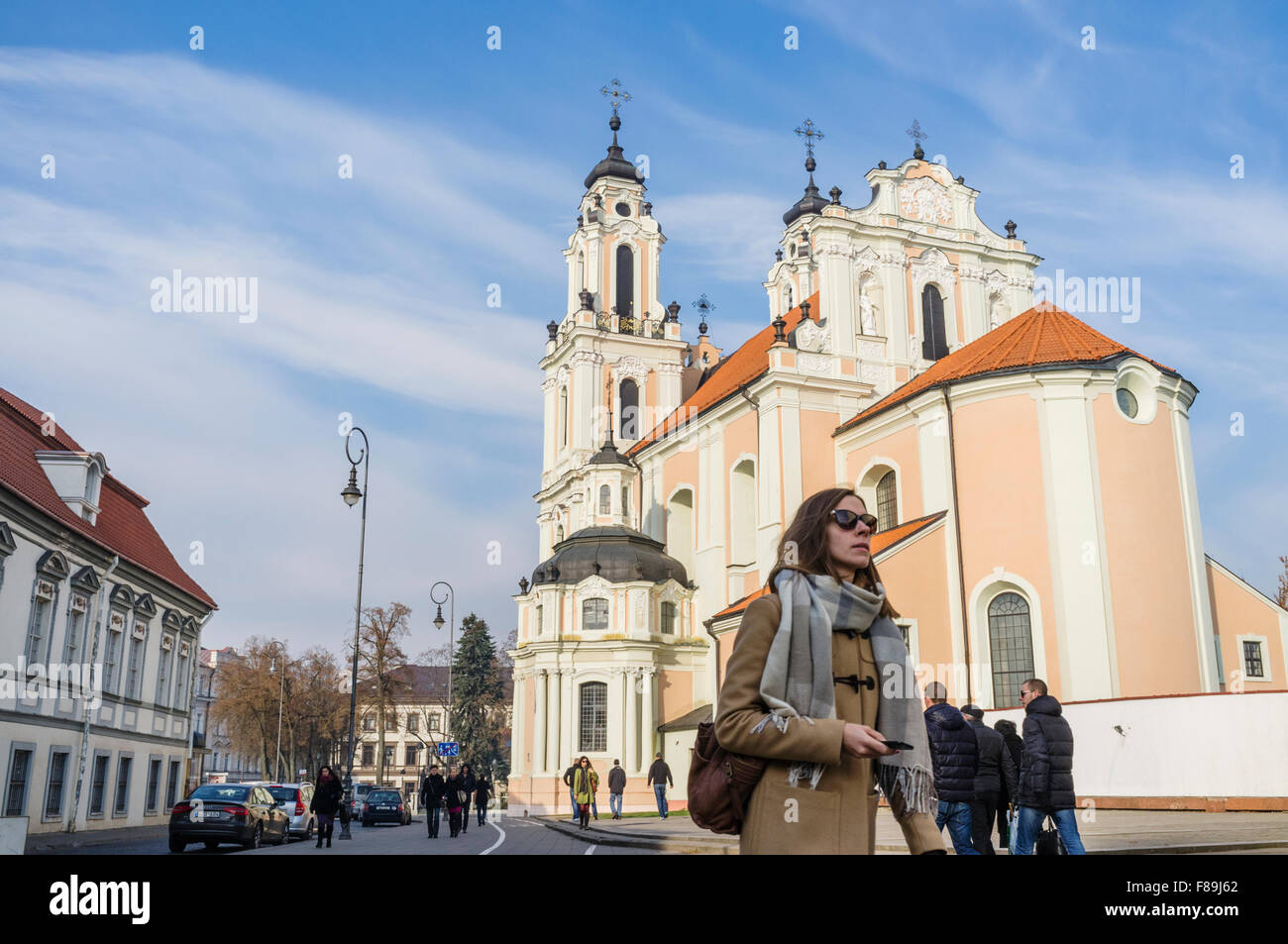 A woman walks past the Church of St. Catherine. Vilnius, Lithuania, Europe - Stock Image