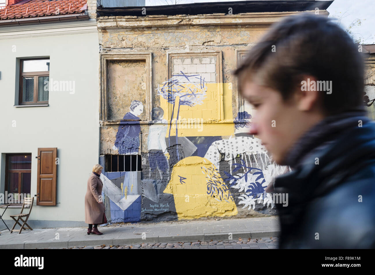 People walk past graffitis at the self-declared independent republic of Uzupis bohemian district. Vilnius, Lithuania - Stock Image