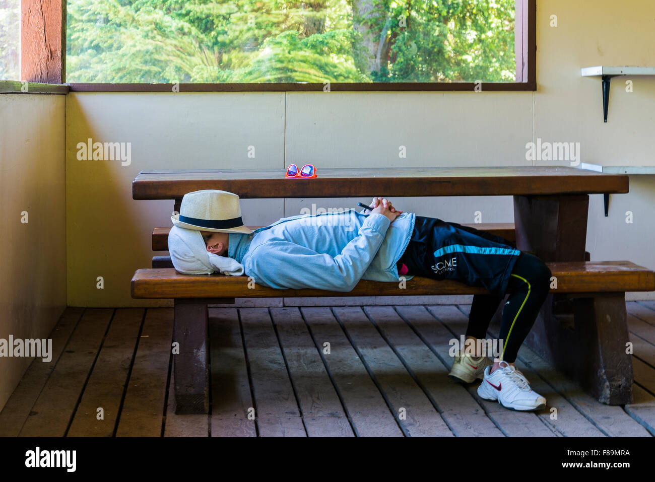 Young man snoozing on a picnic table bench - Stock Image