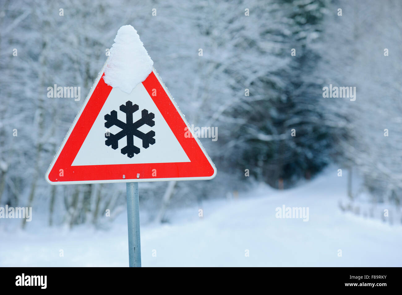 traffic sign warns of snow and ice at road - Stock Image