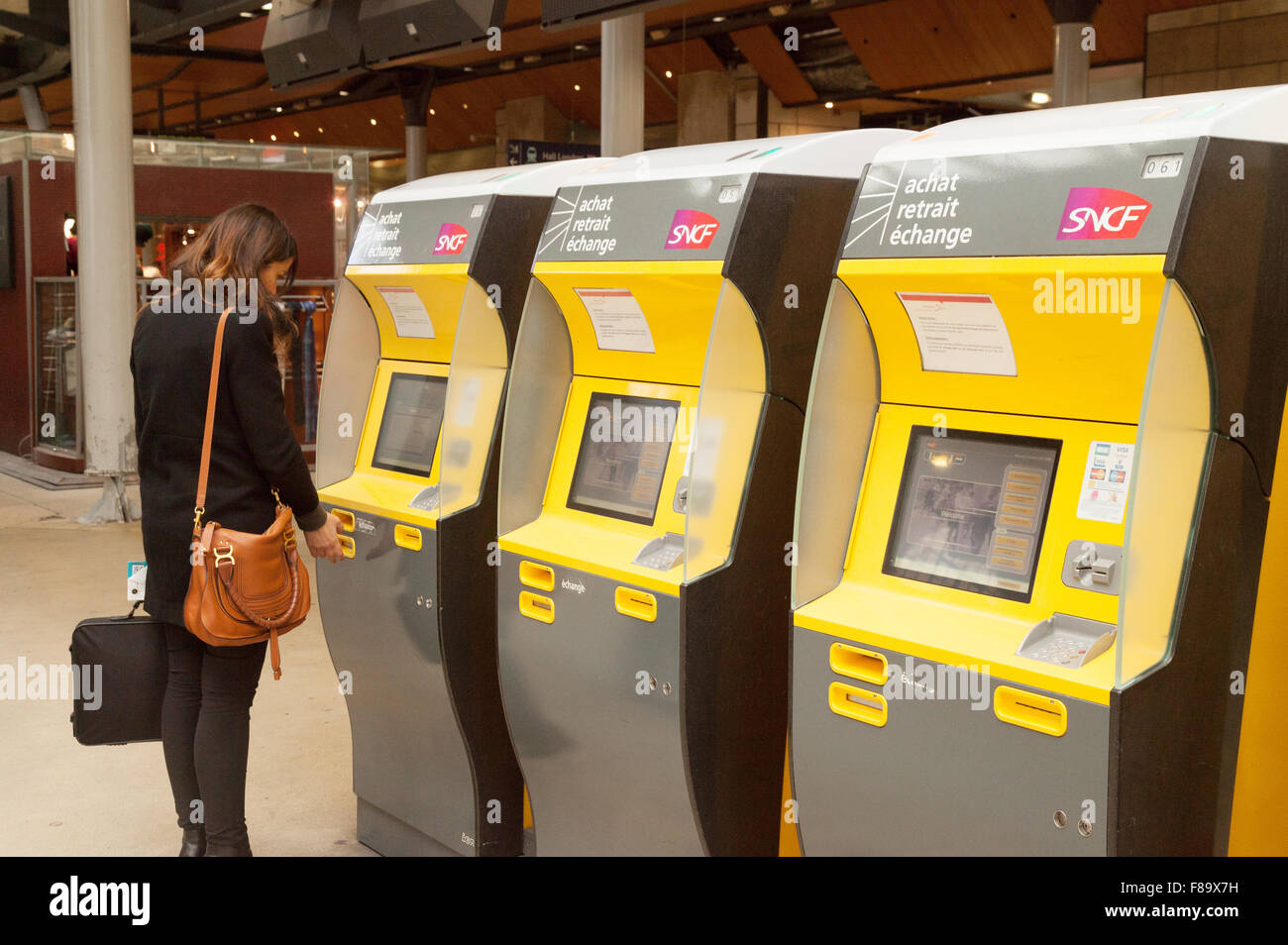 A woman buying a train rail ticket at a ticket machine, Gare du Nord, Paris France Europe - Stock Image
