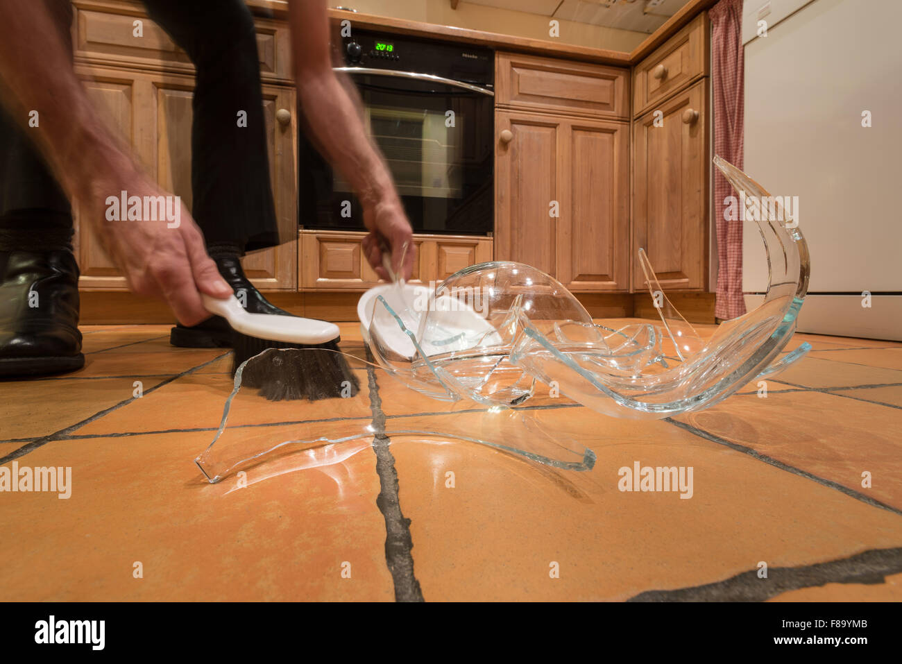 remnants pile of broken glass on floor after accident and pyrex glass bowl slipped out of wet hands knocked over - Stock Image