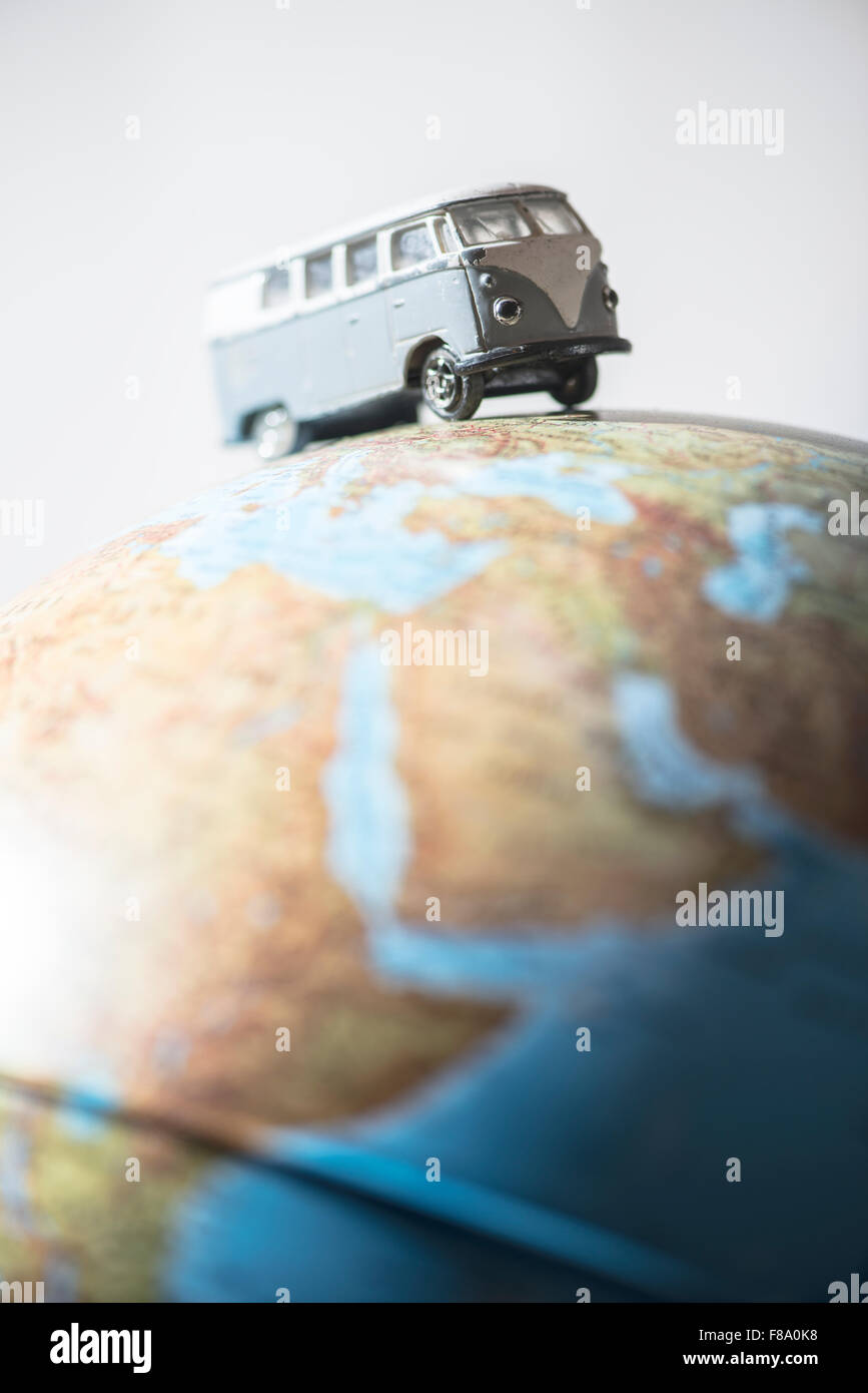 Vintage VW bus on globe. Miniature concept - Stock Image