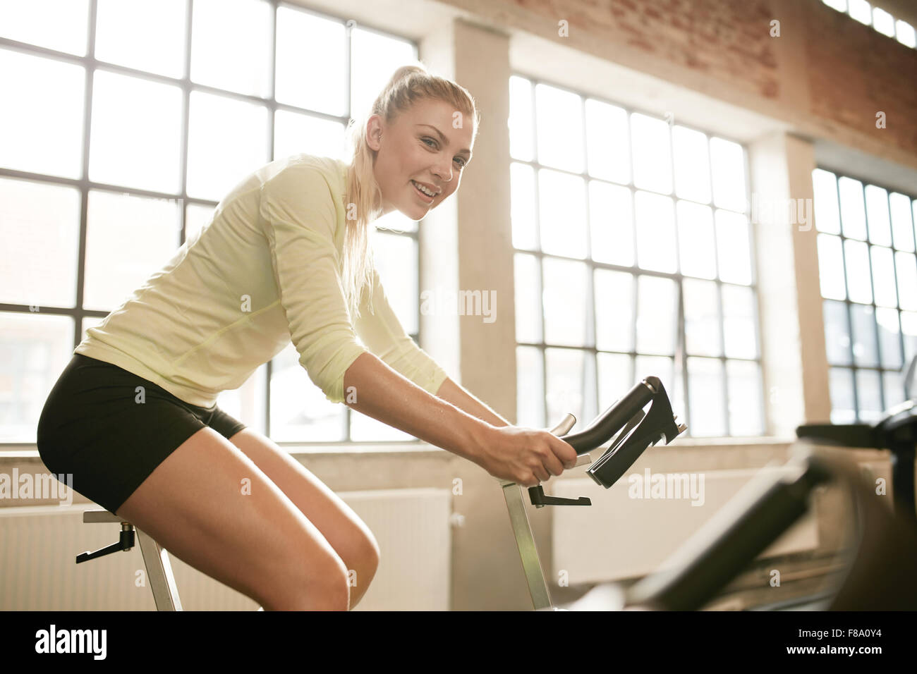 Indoor shot of a sportive woman on bicycle in gym. Young female athlete working out on spinning bike at health club. - Stock Image