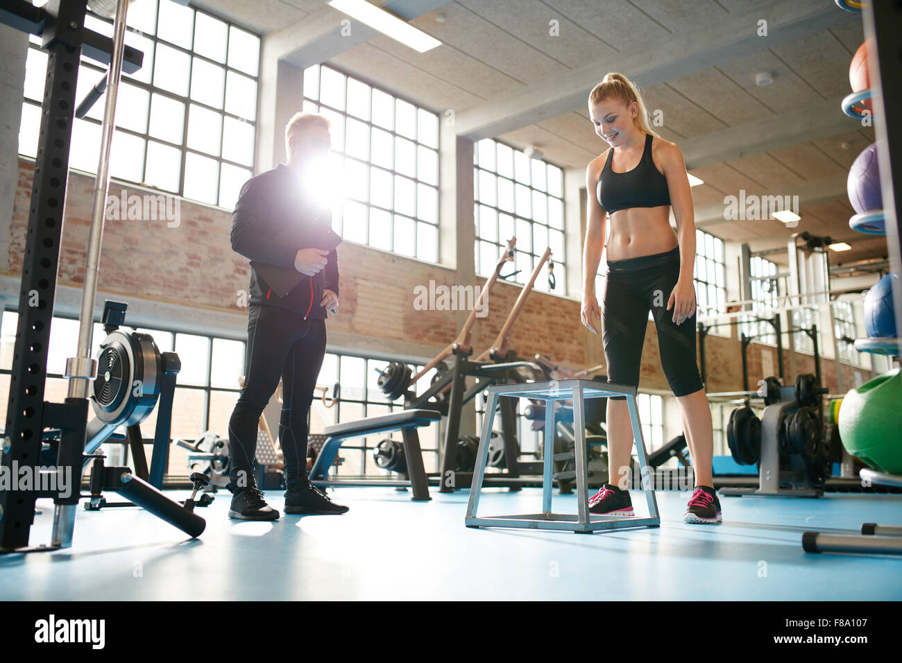 Shot of a young woman exercising in the gym with the supervision of a personal trainer. - Stock Image
