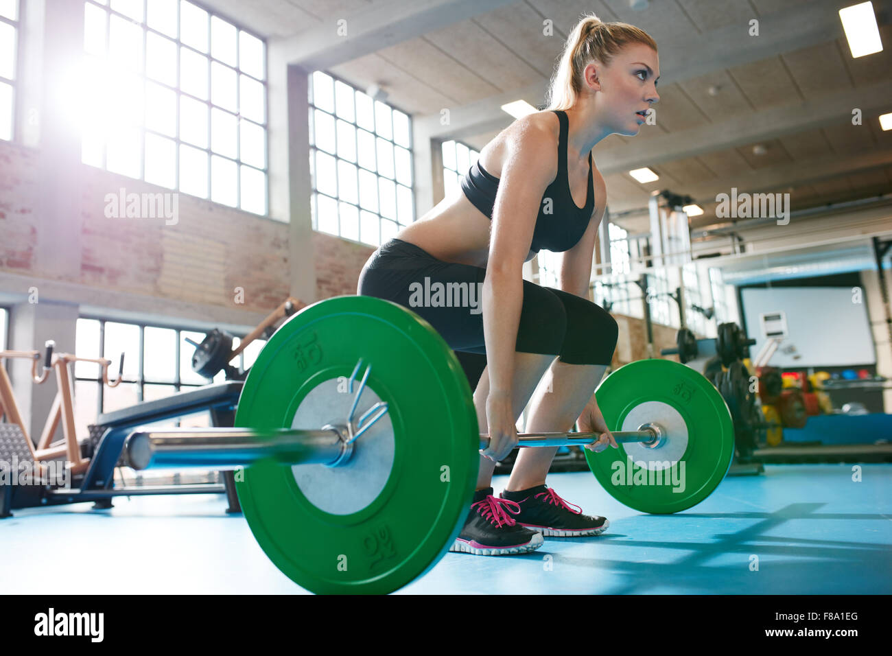 Muscular caucasian woman in a gym doing heavy weight exercises. Young woman doing weight lifting at health club. - Stock Image