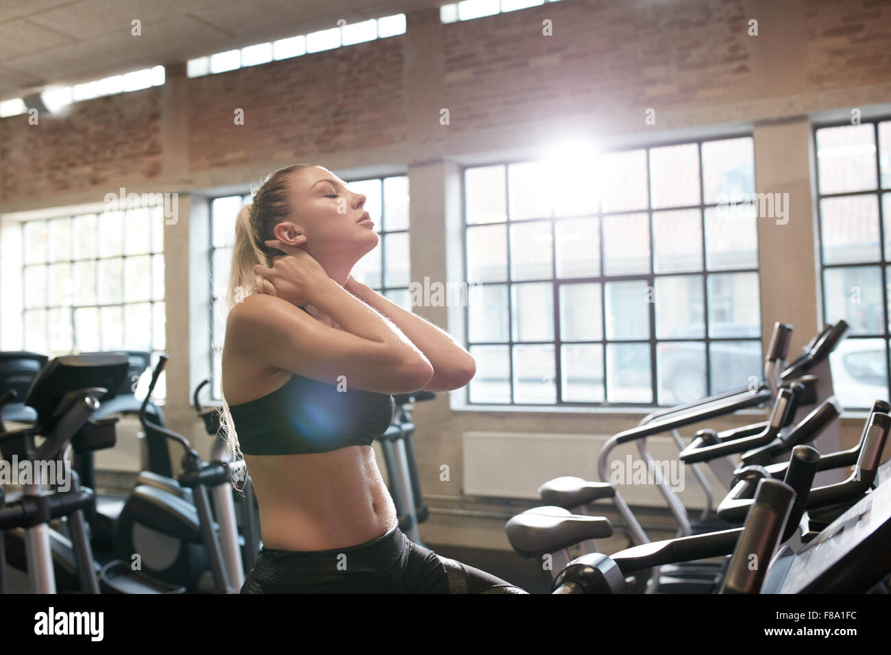 Young woman tired after intense workout on gym bike. Relaxing her neck muscles after workout in fitness club. - Stock Image