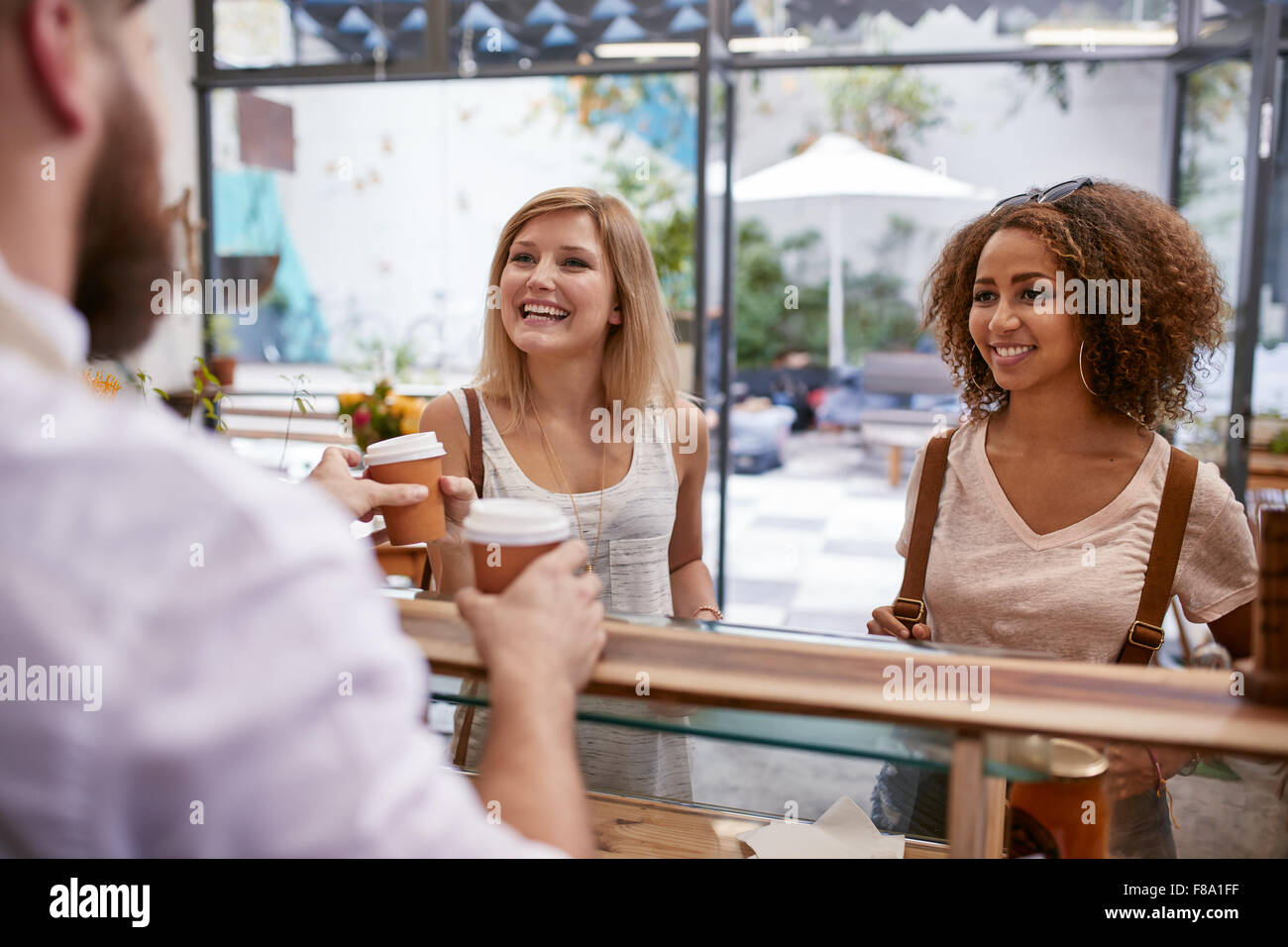 Indoor shot of two young women friends smiles as they receive their hot drinks from the cafe counter. Happy young - Stock Image