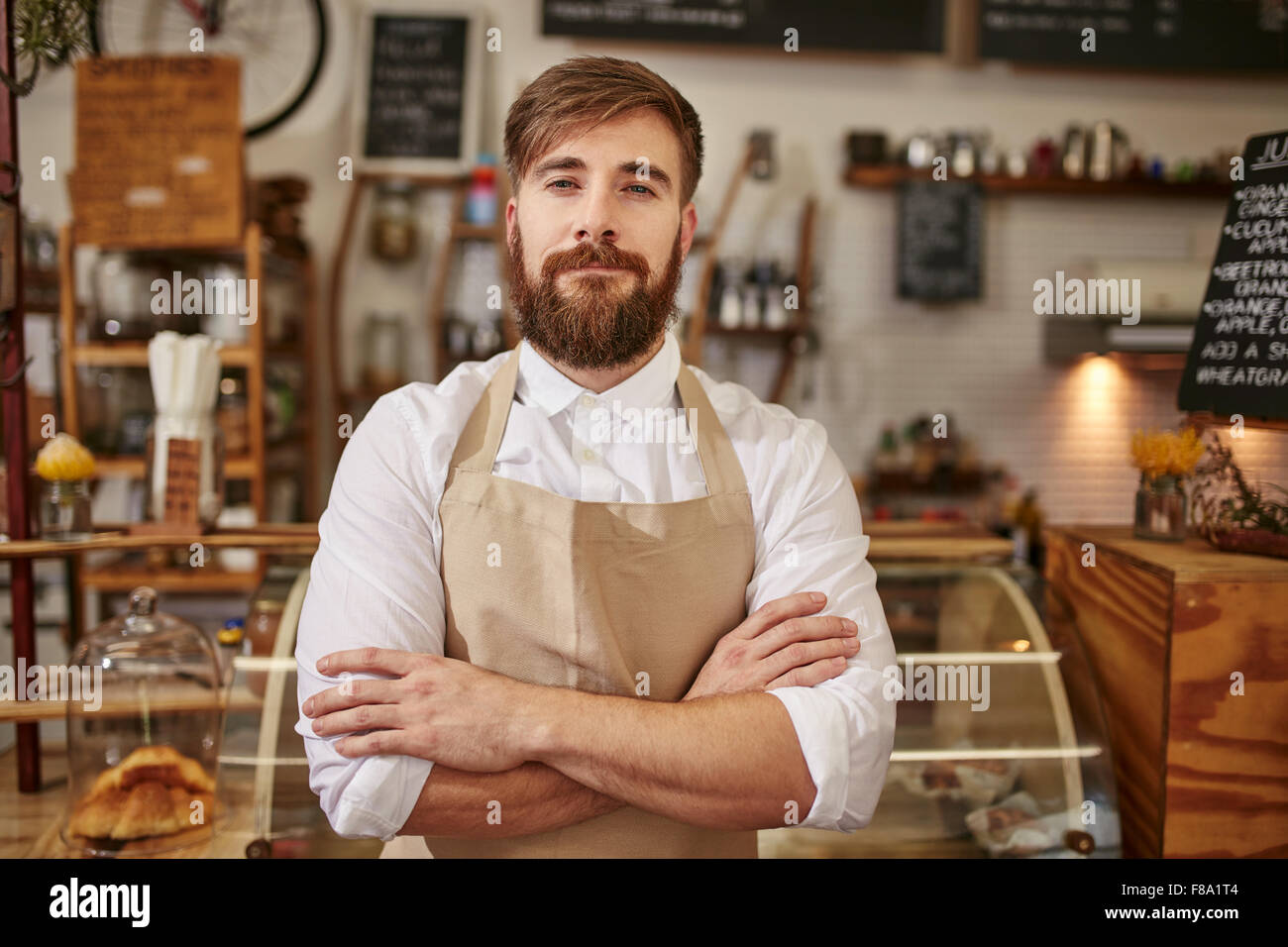 Portrait of young man wearing apron standing with his arms crossed in a coffee shop. Caucasian man with beard standing - Stock Image