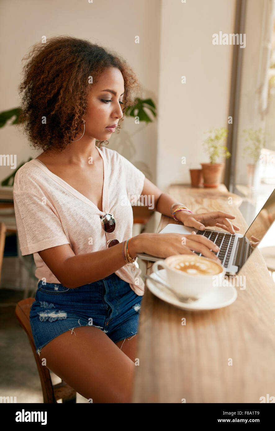Indoor shot of young casual woman sitting in a cafe using laptop. African girl surfing internet on her laptop while - Stock Image