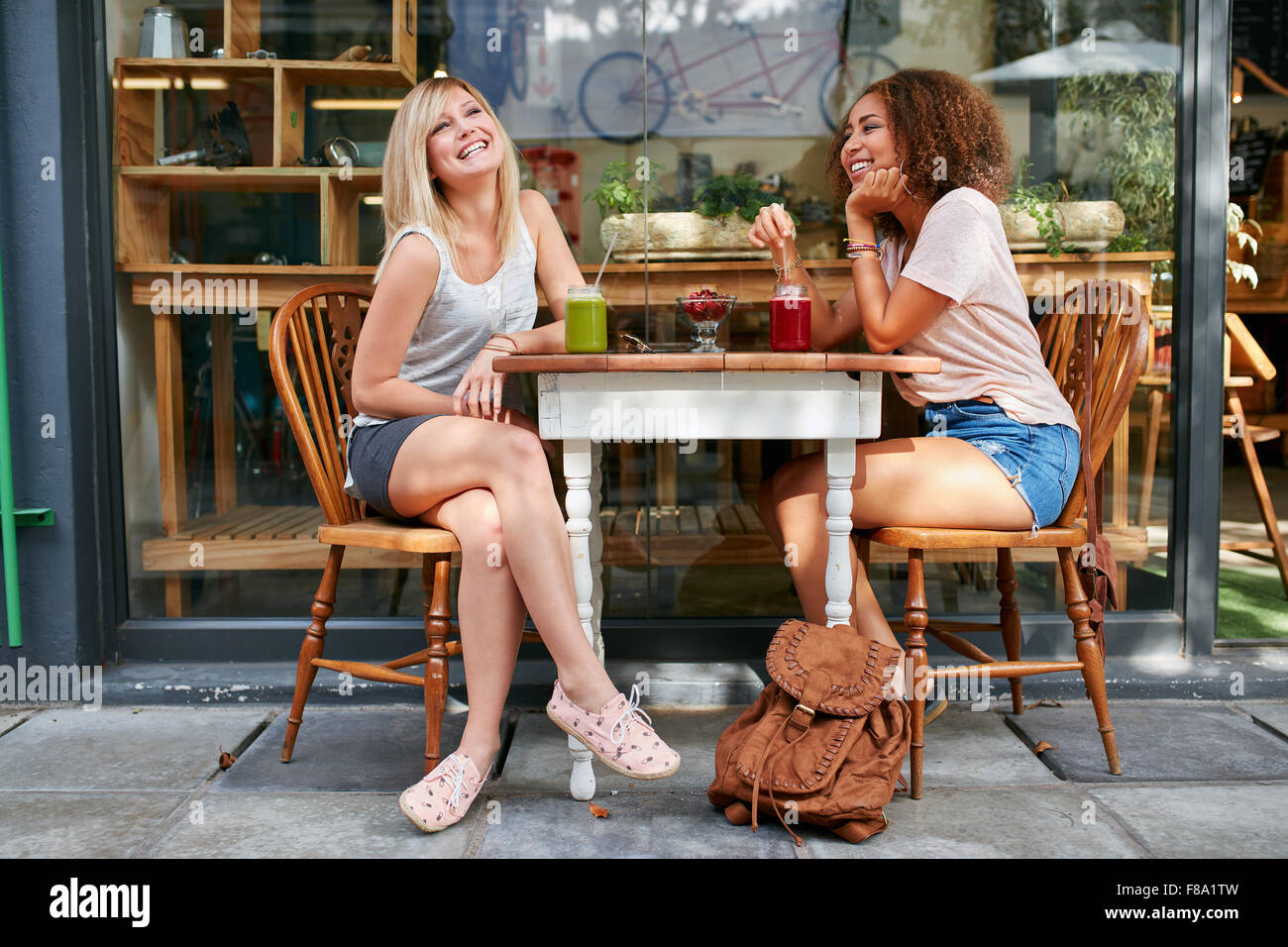 Two young friends sitting at outdoor cafe and smiling. Multiracial women hanging out at sidewalk restaurant. - Stock Image