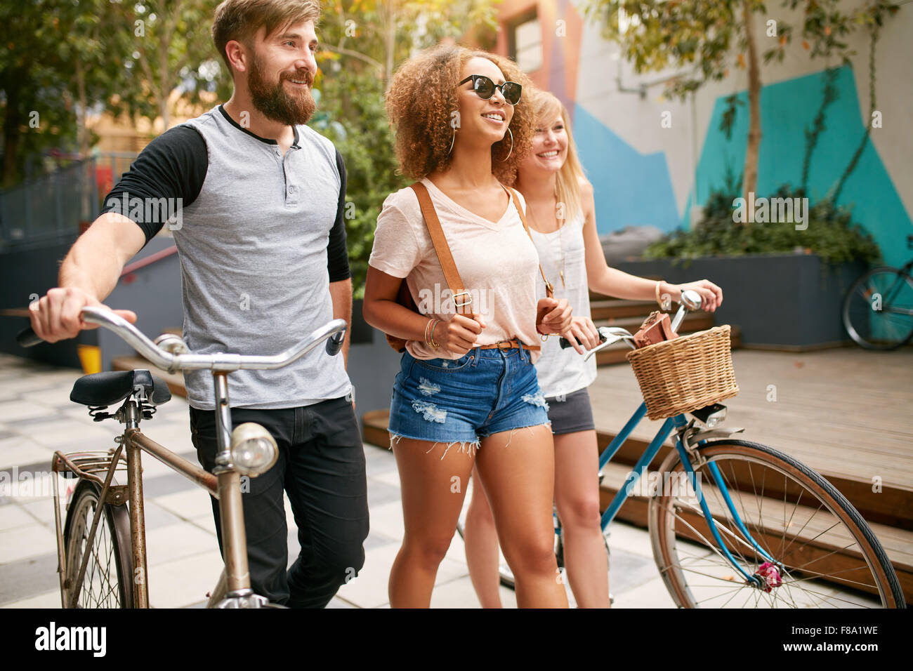 Outdoor shot of young people walking on city street with their bikes. Three friends with bicycles a road. - Stock Image