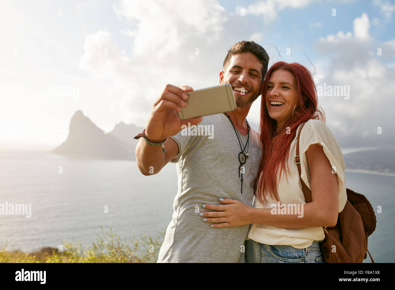Smiling young loving couple taking self portrait outdoors in summer. Young man with his girlfriend taking selfie - Stock Image