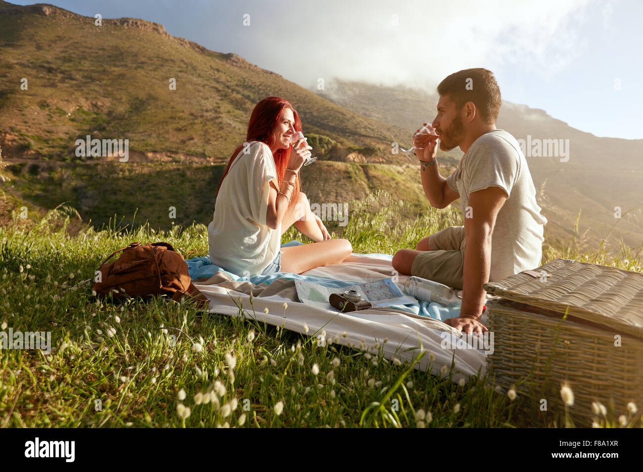 Outdoor shot of a young couple drinking wine. Relaxed man and woman on summer vacation in countryside. - Stock Image