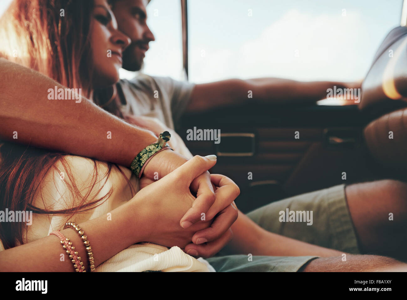 Affectionate young couple sitting in back seat of a car going on road trip. Focus on couple holding hands. - Stock Image