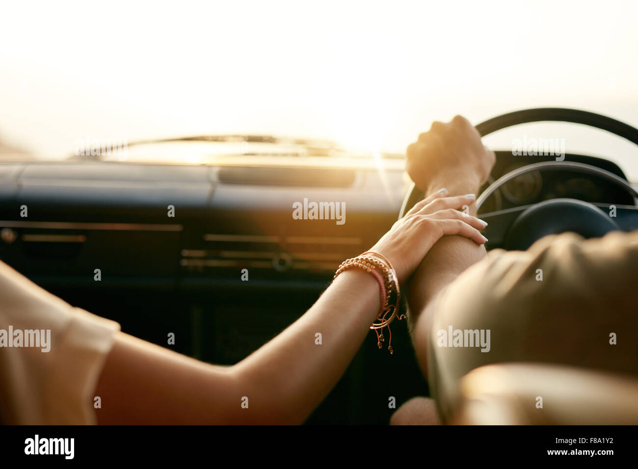 Rear view of a young couple holding hands while sitting in their car together. Man and woman on a road trip. - Stock Image