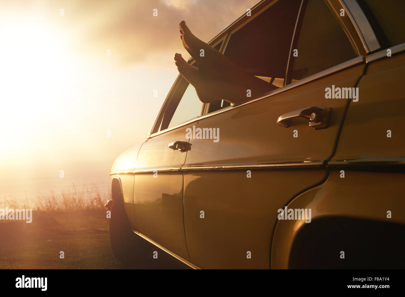 Shot of woman relaxing in a car on road trip. Female feet hanging out of vehicle window at sunset. - Stock Image
