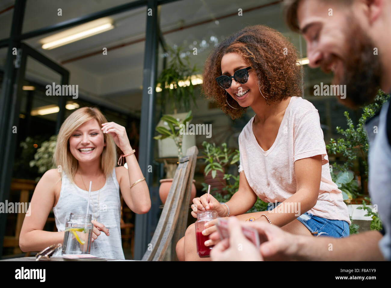 Three friends sitting at sidewalk cafe and playing cards. Relaxed young people at coffee shop enjoying in their - Stock Image