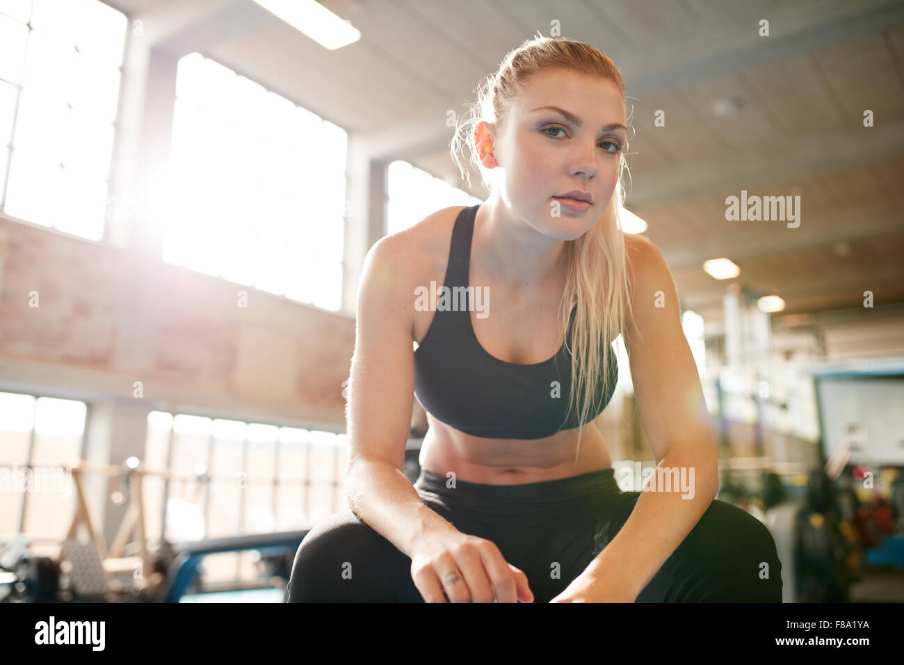 Portrait of attractive young woman sitting relaxed after her workout at gym. Fitness female taking break after exercising - Stock Image