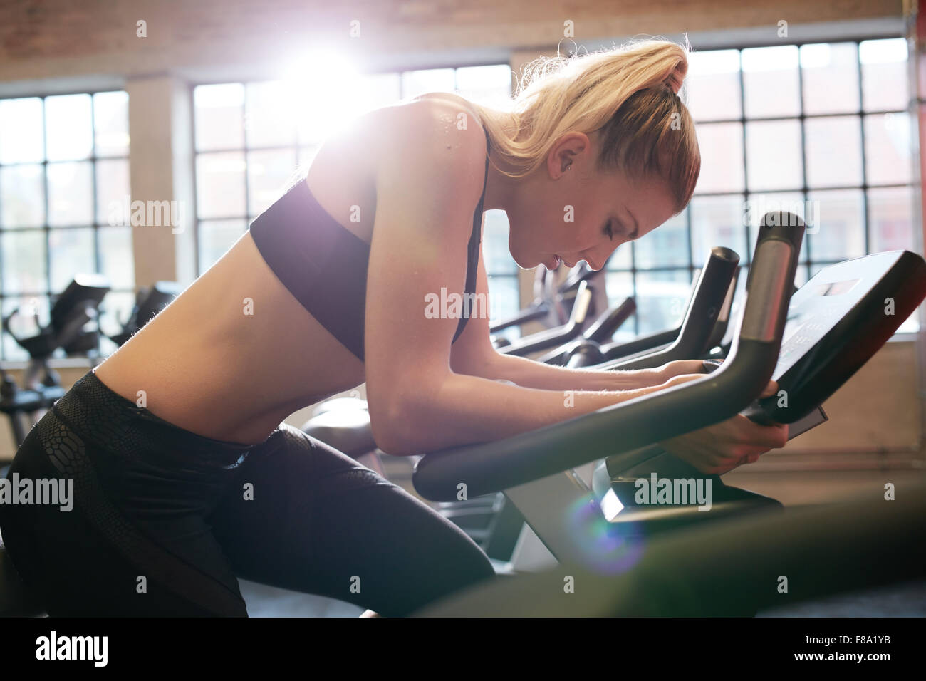 Woman taking break during cycling workout in gym. Female on gym bike doing cardio exercise. - Stock Image